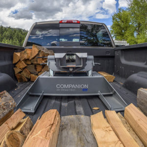 The interior of the back of a truck bed is shown with a BW Companion hitch installed. The truck bed is filled with chopped wood.