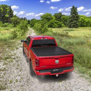 A red truck with a black bed cover drives down a dirt road.