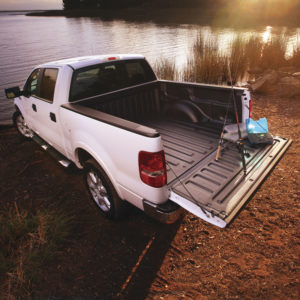 A white pickup truck is parked in front of a lake with a black spray in bed liner and fishing gear in the back.