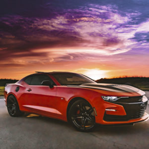 A red Chevrolet sports car is parked in front of a red and orange sunset. The car has dark tinted windows and black custom wheels.