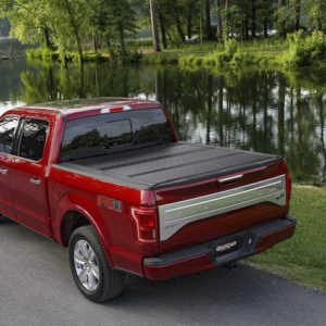 A red truck is shown driving next to a body of water with a black trifold bed cover on the back.